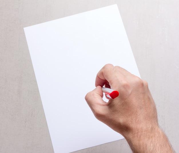 Mão masculina com uma caneta esferográfica e uma folha de papel em branco sobre fundo cinza em branco