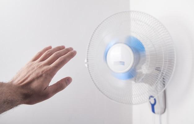 Mão masculina com ventilador elétrico em casa