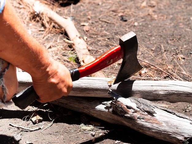 Mão masculina da colheita que corta a madeira com o machado no dia ensolarado