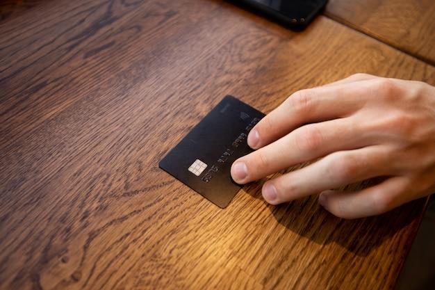 Mão masculina dá um cartão para pagar a conta