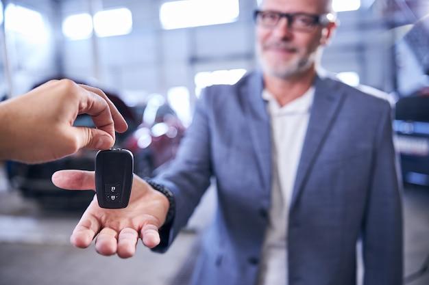 Mão masculina dando a chave do carro inteligente para o motorista na estação de serviço