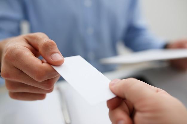Mão masculina de terno dá cartão de visita em branco para outra pessoa