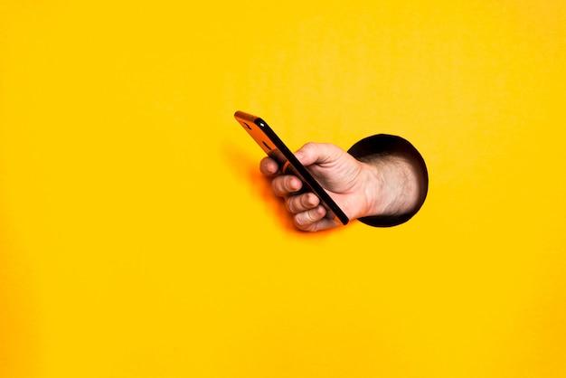 Mão masculina de um buraco em uma parede de papel, segurando um smartphone com uma tela preta.