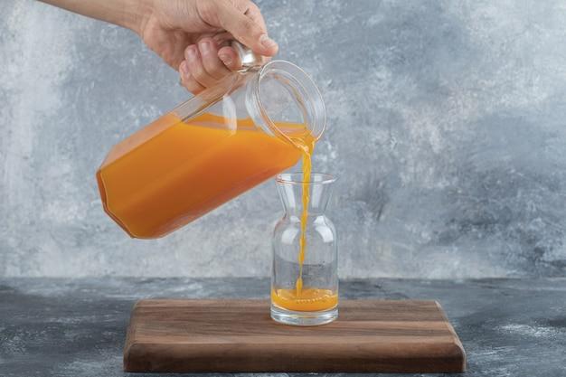 Mão masculina derramando suco de laranja no vidro.