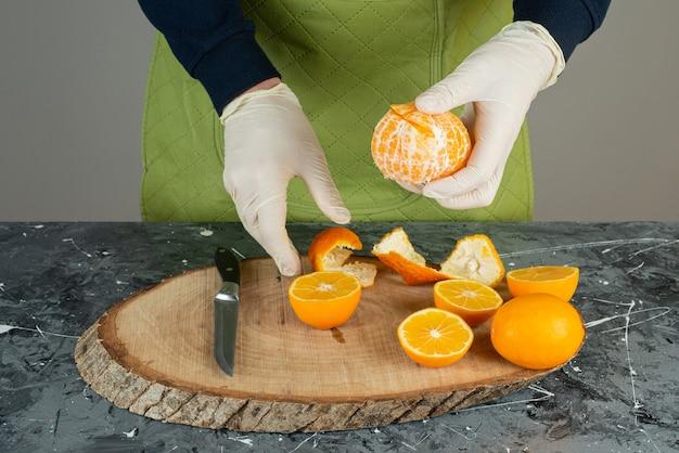 Mão masculina descascando tangerina fresca verde em cima da placa de madeira na mesa.