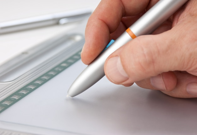 Mão masculina desenha sobre o tablet gráfico