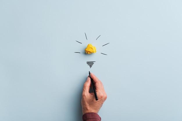 Mão masculina desenhando uma lâmpada sobre fundo azul em uma imagem conceitual.