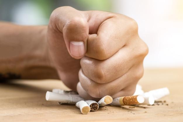 Mão masculina, destruindo cigarros - parar de fumar conceito