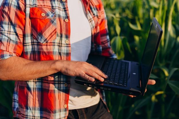 Mão masculina do close up no portátil. fazendeiro que está em um caderno aberto da terra arrendada do campo.