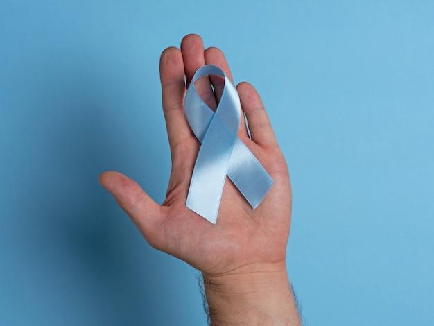 Mão masculina do close-up que guarda a fita azul da conscientização do câncer de próstata em um fundo azul brilhante. conceito de medicina e saúde