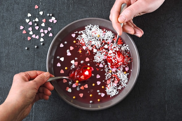 Mão masculina e feminina com colheres de comer marmelada vermelha da tigela, decorada para o dia dos namorados.
