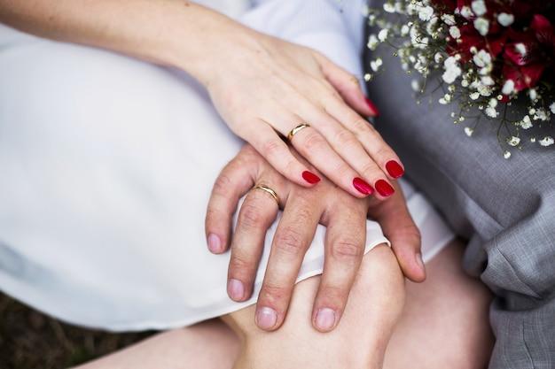 Mão masculina e feminina com um anel de casamento, uma mão feminina com unhas vermelhas