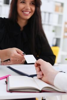 Mão masculina em camiseta preta dá cartão de visita ao visitante