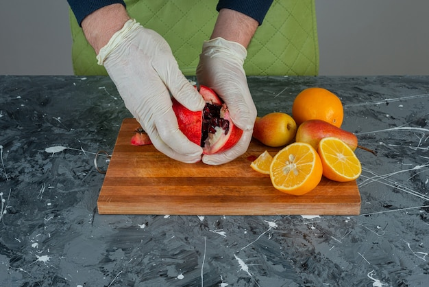 Mão masculina em luvas cortando romã vermelha na mesa de mármore.