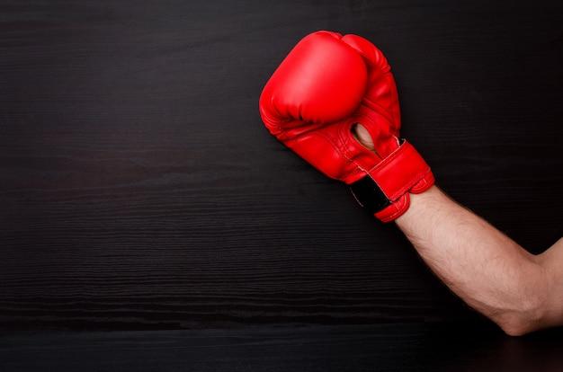 Mão masculina em luvas de boxe vermelhas em um preto na lateral do quadro,