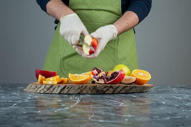 Mão masculina em luvas de corte de maçã vermelha na mesa de mármore.