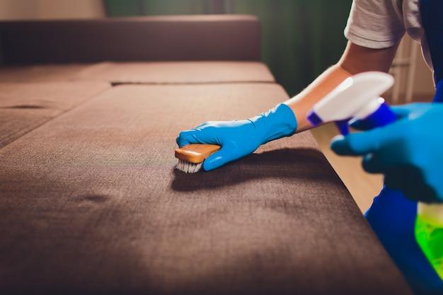 Mão masculina em luvas de proteção azuis claras, limpeza do sofá do sofá