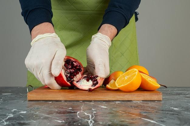 Mão masculina em luvas quebrando a romã vermelha na mesa de mármore.