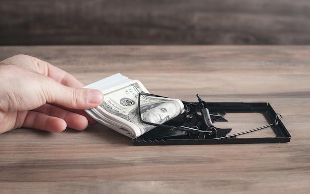 Mão masculina em uma ratoeira e dólares. risco