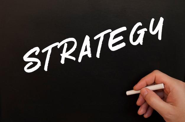 Mão masculina escreve com giz as palavras estratégia em um quadro negro.
