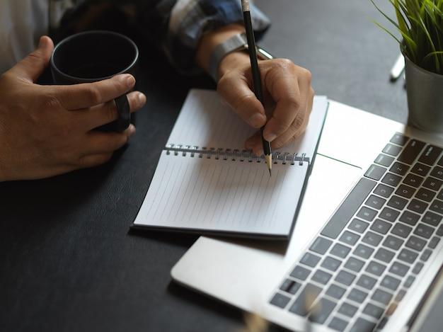 Mão masculina escrevendo no caderno enquanto trabalha com o laptop e segurando a xícara de café na mesa de trabalho