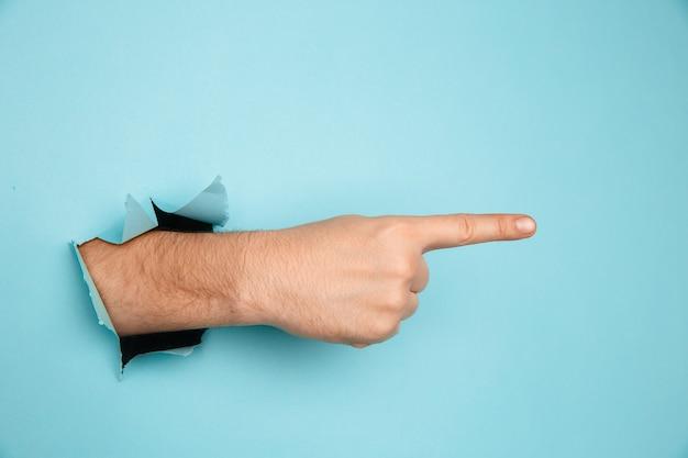 Mão masculina, fazendo sinal através de um buraco no papel isolado sobre fundo azul.