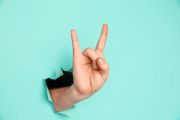 Mão masculina fazendo um gesto de rock and roll, festa, cabra sobre um fundo azul