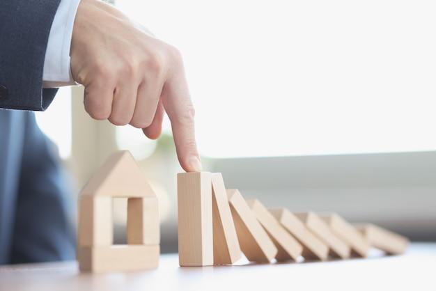 Mão masculina impedindo a queda de blocos de madeira na frente da casa de brinquedo, closeup