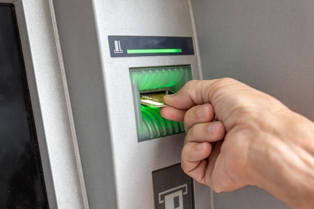 Mão masculina inserindo cartão de crédito no caixa eletrônico