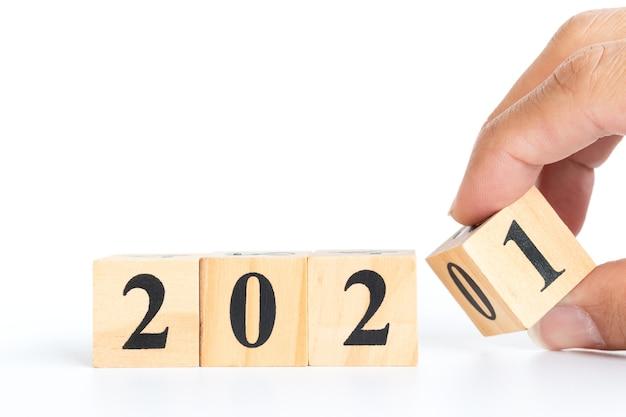 Mão masculina lançando blocos de madeira para o número de mudança de 2020 a 2021. conceito de ano novo