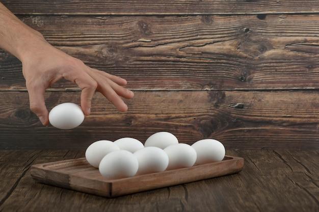 Mão masculina levando ovo cru orgânico da placa de madeira.