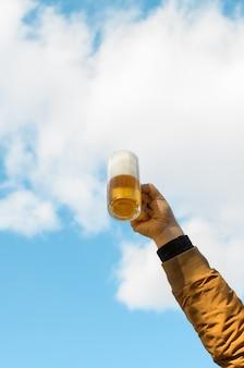 Mão masculina, levantando uma caneca de cerveja em aplauso contra o céu azul nublado lá fora. foto vertical