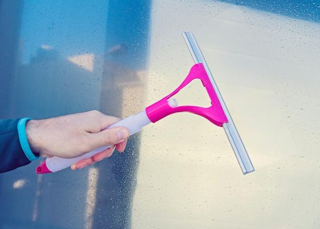 Mão masculina limpa janela de vidro com rodo de limpador de janela
