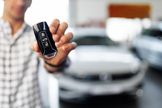 Mão masculina mostrando as chaves do carro contra um novo carro de luxo na concessionária