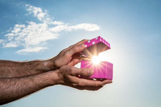 Mão masculina mostrando caixa de presente rosa com fundo de céu azul. conceito de dia dos namorados. pequenas caixas de presente artesanal na noite azul brilhante.