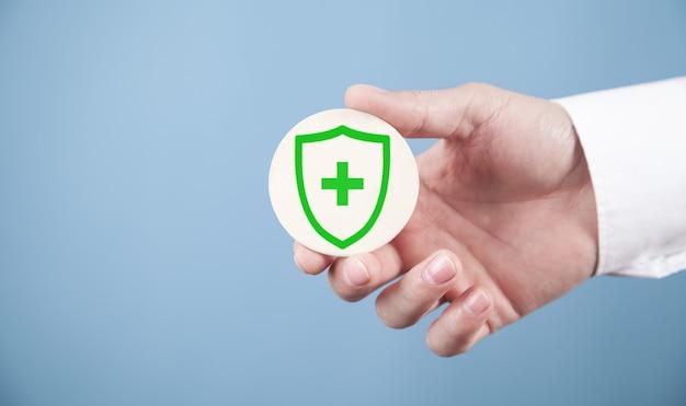 Mão masculina mostrando escudo com cruz. proteção de saúde médica