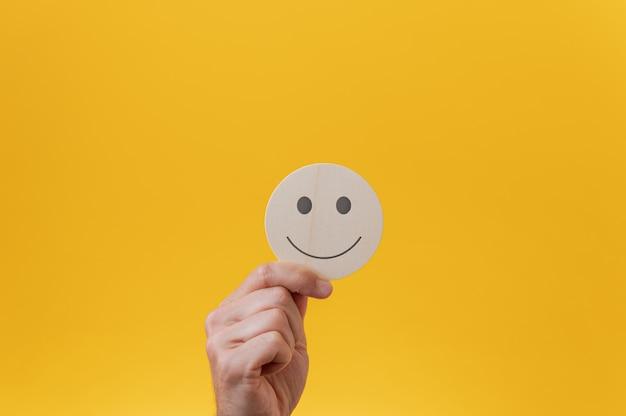 Mão masculina mostrando um círculo de corte de madeira com um rosto sorridente