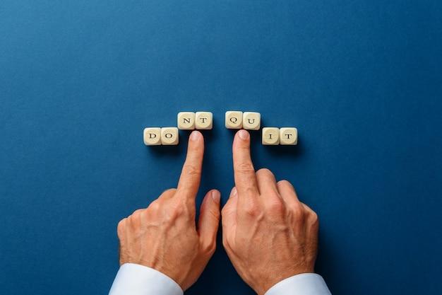 Mão masculina, mudando um não desista em um sinal de faça isso escrito em dados de madeira. sobre fundo azul escuro.