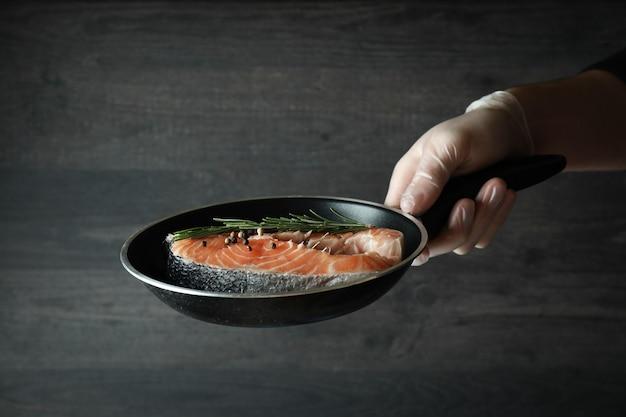 Mão masculina na luva segurando a panela com carne de salmão, close-up