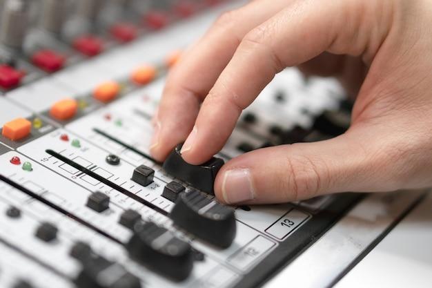 Mão masculina no controle fader no console. mesa de mistura de estúdio de gravação de som com engenheiro ou produtor musical.