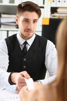 Mão masculina no terno dá cartão de visita em branco ao visitante