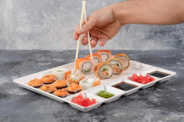 Mão masculina pegando sushi roll com pauzinhos no prato branco