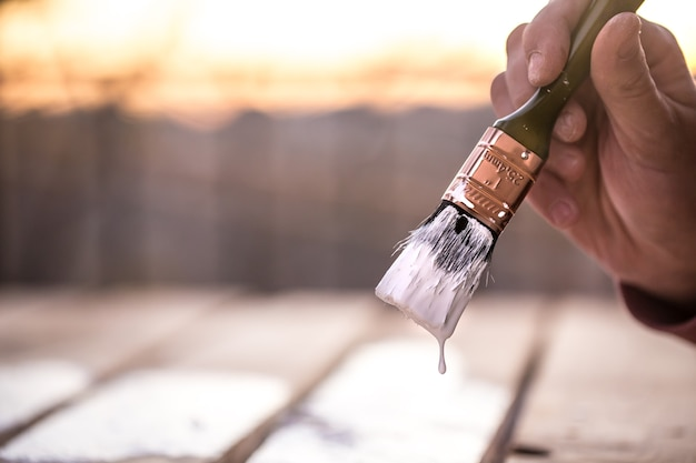Mão masculina pinta com tinta branca na madeira, conceito de pintura, close-up, lugar para texto