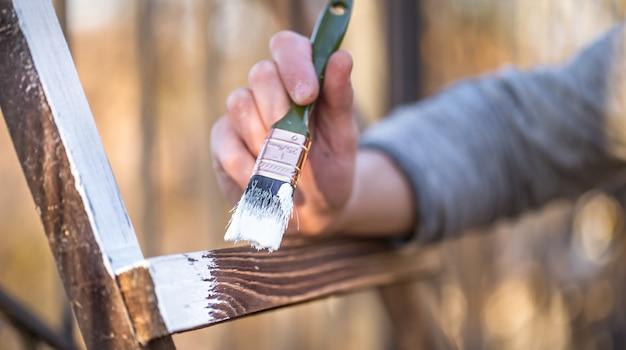 Mão masculina pinta com tinta branca na madeira