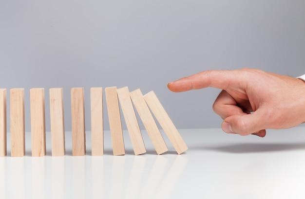 Mão masculina pronta para empurrar o dominó