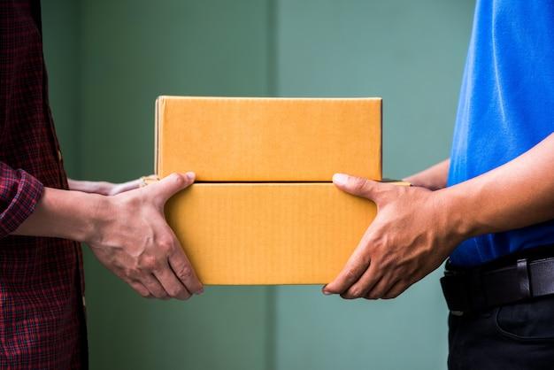 Mão masculina que aceita uma entrega das caixas do entregador.