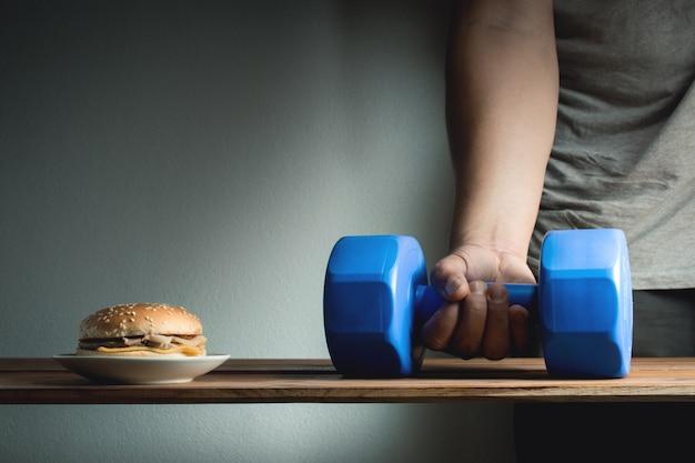 Mão masculina que alcança para pegarar exercícios da ideia do peso para o conceito da dieta da perda de peso.