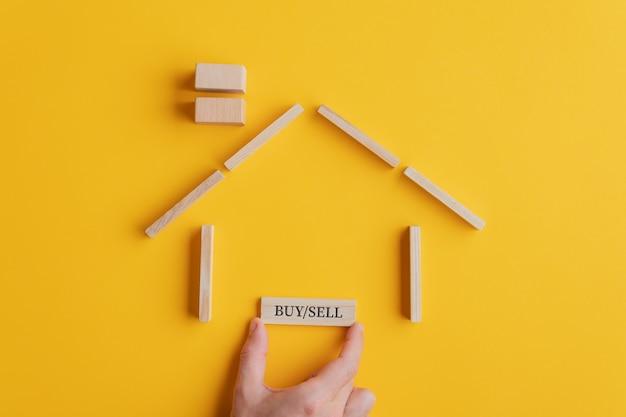 Mão masculina que coloca uma placa de compra / venda em uma casa feita de blocos de madeira e pinos em uma imagem conceitual do mercado imobiliário. sobre fundo amarelo.