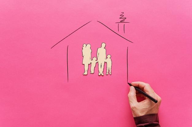 Mão masculina que desenha a forma de uma casa em torno de um papel recortou a silhueta de uma família de cinco pessoas em uma imagem conceitual de segurança e abrigo