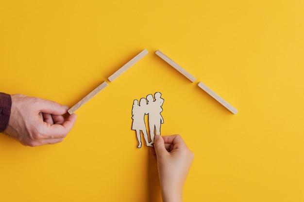 Mão masculina que faz um telhado de estacas de madeira para uma criança colocar a silhueta da família de corte de papel sob ele. imagem conceitual de segurança e proteção. sobre fundo amarelo.